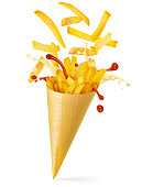 french fries, mayo and ketchup spilling out of a paper cone isolated on white