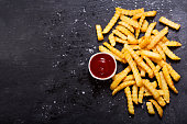 French fries with ketchup on dark table, top view