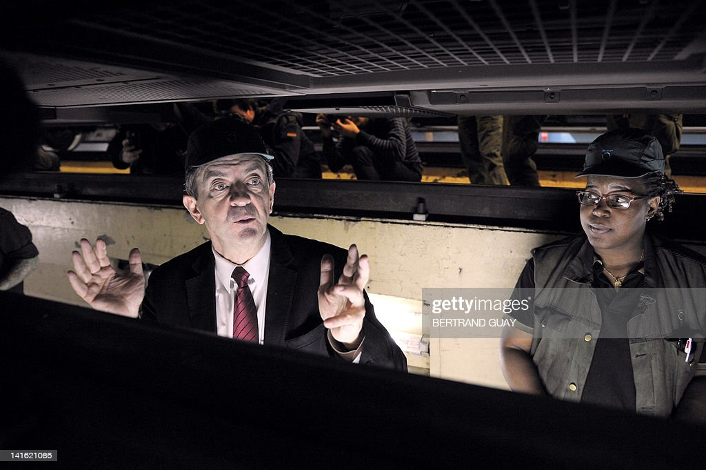 French Front de Gauche candidate for the 2012 French presidential election, Jean-Luc Melenchon (L), gestures as he looks at the chassis of a RER train (Regional Express Network) in a RATP workshop in Massy, Paris suburb, before a meeting with an unions delegation of the RATP (Autonomous Operator of Parisian Transports) on March 20, 2012.