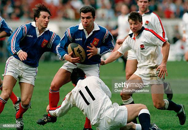 French fullback JeanLuc Sadournay is tackled by Rory Underwood of England watched by Philippe Sella of France and Rob Andrew of England during the...