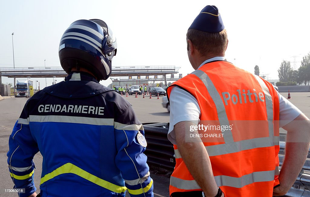 A French gendarme (L) and a Belgian police officer check vehicles at a toll station in Fresnes-les-Montauban, near Arras northern France, on July 6, 2013, working in collaboration with Dutch and English police officers during the first wave of departures for the summer holiday. AFP PHOTO / DENIS CHARLET
