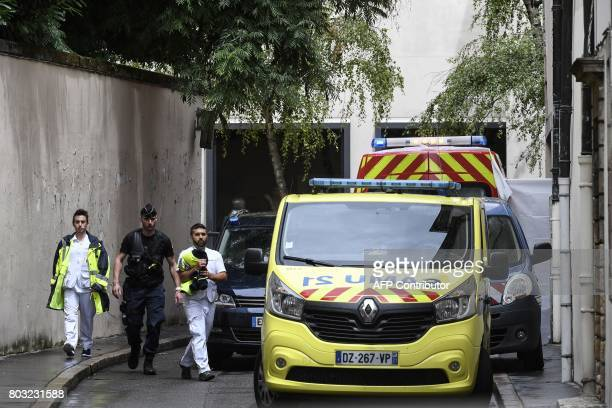 A French gendarme and medics walk outside the courthouse of Dijon on June 29 where Murielle Bolle is being heard for complicity in the murder of the...