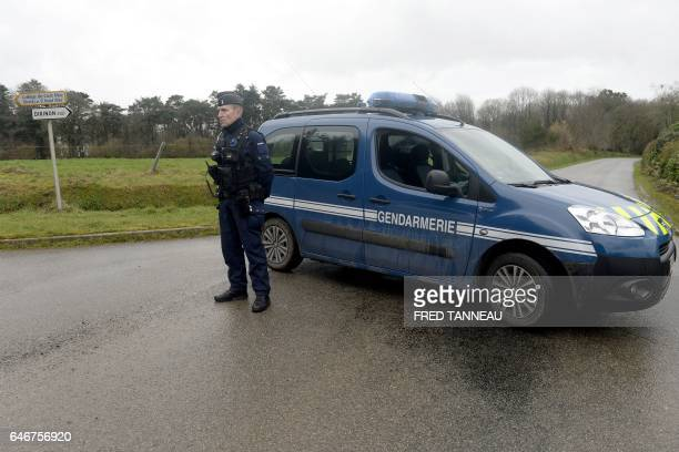 A French gendarme blocks the access to a road where a healthcare card in the name of Charlotte Troadec has been discovered by a runner on March 1 in...