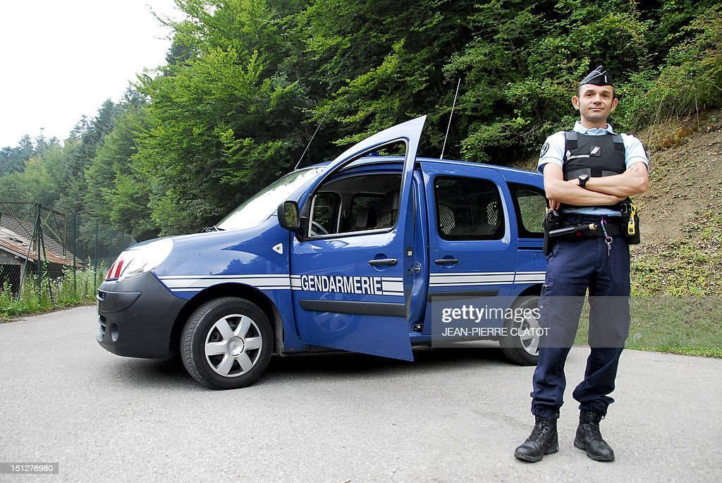 A French gendarme blocks the road leading to the scene where four people died in a shooting at a parking near the Annecy Lake, eastern France, including three found in the same British registered car, on September 5, 2012. Firemen were first to arrive on the scene and found the three bodies in the car. The fourth victim, a cyclist, was found nearby along with a seriously wounded young girl.