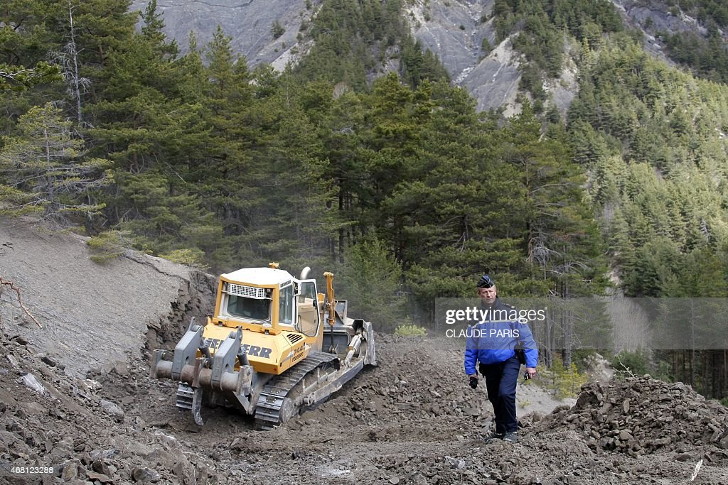 French Gendarme Bruno Hermignies stands by a bulldozer clearing a path to the crash site of the Germanwings Airbus A320 near SeynelesAlpes France on...