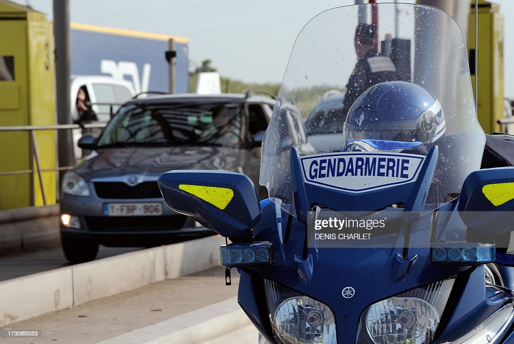 A French gendarme checks vehicles at a toll station in Fresnes-les-Montauban, near Arras northern France, on July 6, 2013, working in collaboration with Belgian, Dutch and English police officers during the first wave of departures for the summer holiday.