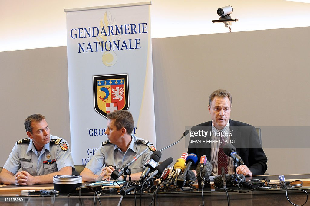 French gendarme colonel Benoit Vinneman and lieutenant colonel Bertrand Francois listen to French Annecy's prosecutor, Eric Maillaud, giving a press conference at the courthouse of the southeastern French city of Annecy on Septembre 6, 2012, after four people were shot dead in or close to a British-registered car that was found in a forest car park on the edge of the French Alpine village of Chevaline. The car, a BMW, contained the bodies of a man, in the front, and two women who were seated in the back, police said.