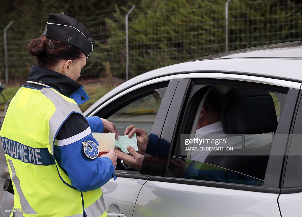 A French gendarme controls a driver on December 28, 2012 at the Fleury-en-Bière's toll.