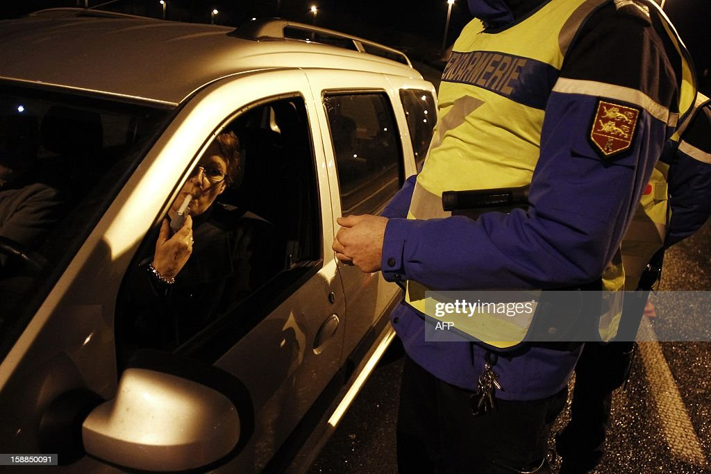 A French gendarme controls a driver with a breathalyzer during the New Year's night on January 1, 2013 in Breteville-sur-Odon, near the northwestern city of Caen.