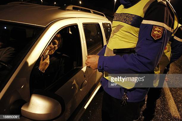 A French gendarme controls a driver with a breathalyzer during the New Year's night on January 1 2013 in BretevillesurOdon near the northwestern city...