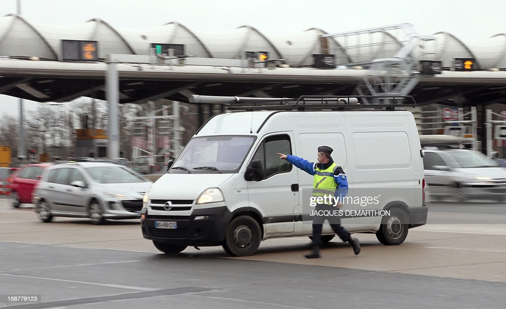 A French gendarme controls a vehicle on December 28, 2012 at the Fleury-en-Bière's toll.