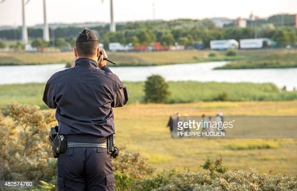 A French gendarme films the migrants who try to enter inside the Eurotunnel site in Coquelles near Calais northern France on July 31 2015 The...