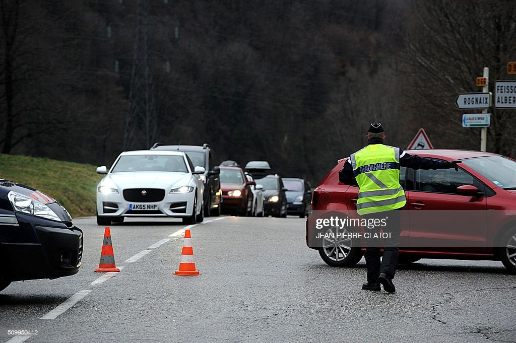 A French gendarme force vehicles to leave the departemental road to take the RN 90 road on February 13, 2016 near Cevins in the French Alps, during a crossover of people going to or coming from the ski stations during the school holidays. CLATOT