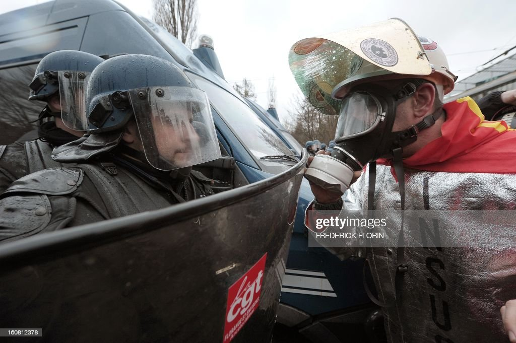 A French Gendarme from an anti-riot unit faces a protestor on February 6, 2013, during a demonstration of workers from several European Arcelormittal steel plants near the European Parliament in Strasbourg, eastern France. The world's top steel producer ArcelorMittal stumbled into the red last year with a net loss of $3.72 billion (2.75 billion euros) largely due to costs related to Europe.