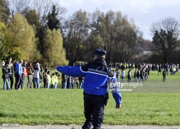 A French gendarme gestures by a group of citizens taking part in a search operation on October 30 2017 in Gray northeastern France two days after...
