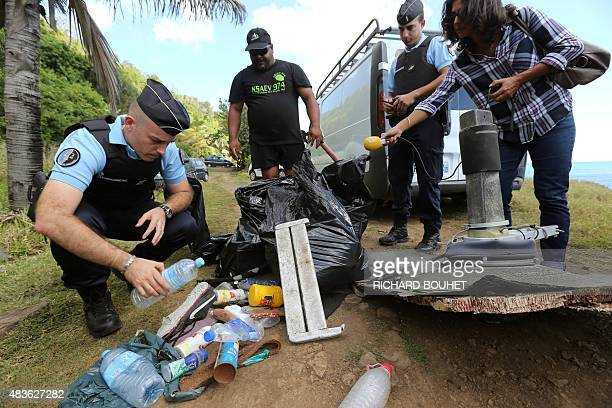 A French Gendarme inspects debris gathered by members of local ecological associations and volunteers on August 11 2015 in the eastern part of...