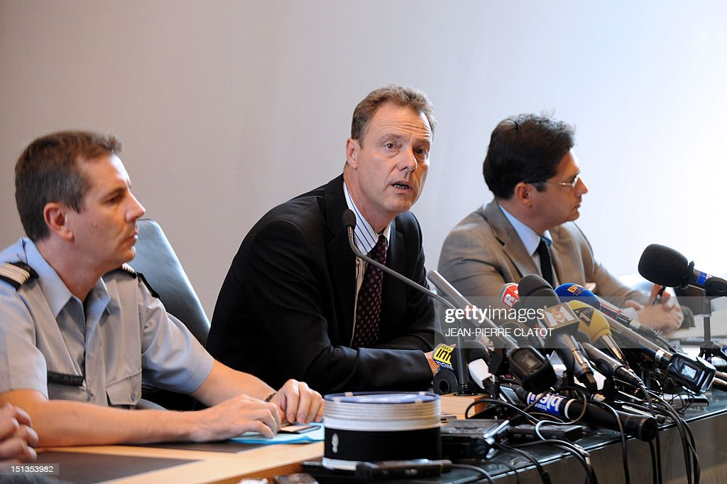 French gendarme lieutenant colonel Bertrand Francois (L) listens to French Annecy's prosecutor, Eric Maillaud (C) giving a press conference at the courthouse of the southeastern French city of Annecy on Septembre 6, 2012, after four people were shot dead in or close to a British-registered car that was found in a forest car park on the edge of the French Alpine village of Chevaline. The car, a BMW, contained the bodies of a man, in the front, and two women who were seated in the back, police said.