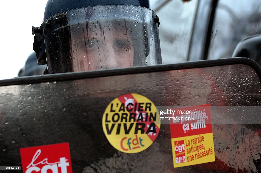 A French Gendarme looks on behind his shield as he faces demonstrators on February 6, 2013, during a protest of workers from several European Arcelormittal steel plants near the European Parliament in Strasbourg, eastern France. The world's top steel producer ArcelorMittal stumbled into the red last year with a net loss of $3.72 billion (2.75 billion euros) largely due to costs related to Europe.