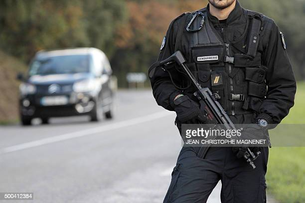 A French gendarme patrols on the road on December 8 2015 in La Mole near SaintTropez southeastern France as they search for the man who injured a...