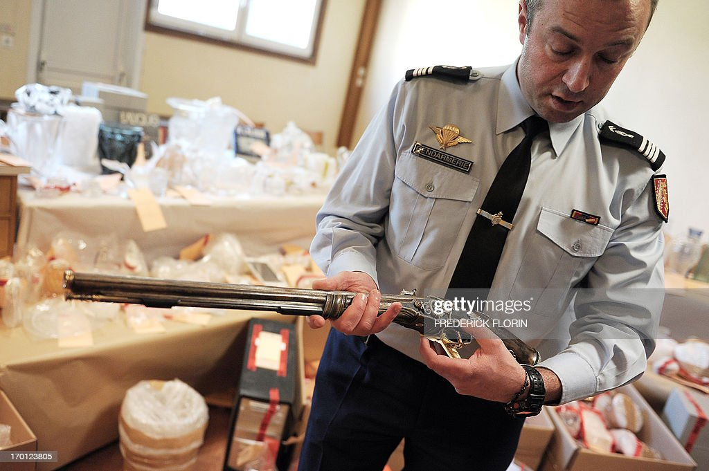 A French gendarme shows an item seized during the recent break up of art works traffickers from a plant of French luxury manufacturer Lalique, in Saverne, eastern France, on June 7, 2013.