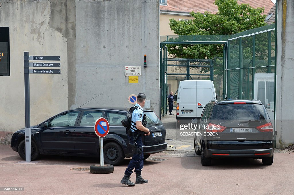 A French gendarme stands guard as vehicles drive into the Ensisheim prison, northeastern France, where a psychologist is taken hostage by a prisoner on June 30, 2016. / AFP / SEBASTIEN