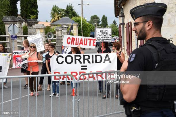 A French gendarme stands guard in front of protesters during a demonstration against bullfighting on June 24 2017 in the French city of La Brede...