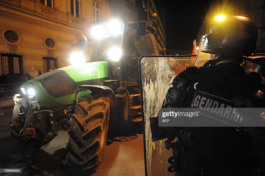 A French Gendarme stands guard in front of the Sarthe prefecture where a tractor arrives to discharge used tires late on January 15, 2013 in Le Mans, western France during a protest called by farmers union FNSEA against new constraints arising from the applications of European Union rules against nitrates. A new map identifies 'vulnerable areas' to nitrates which require special protection to not pollute water resources.