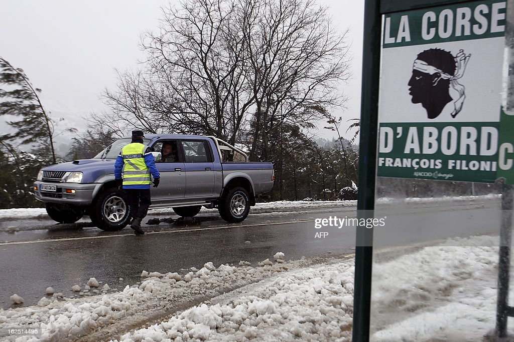 A French gendarme stops a car to control snow equipment on a snow covered road near Ajaccio on February 24, 2013, in Corsica.