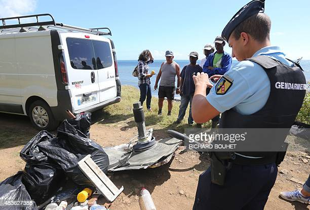A French Gendarme takes a picture of debris gathered by members of local ecological associations and volunteers on August 11 2015 in the eastern part...