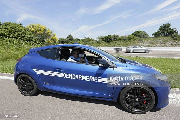 A French gendarme uses a radar gun to check the speed of cars driving on July 6 2013 during a traffic control and survey on the A6A31 highway in...