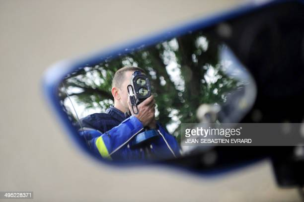 A French gendarme using a radar gun to check the speed of passing cars is seen reflected in the wing mirror of a police car during a traffic control...