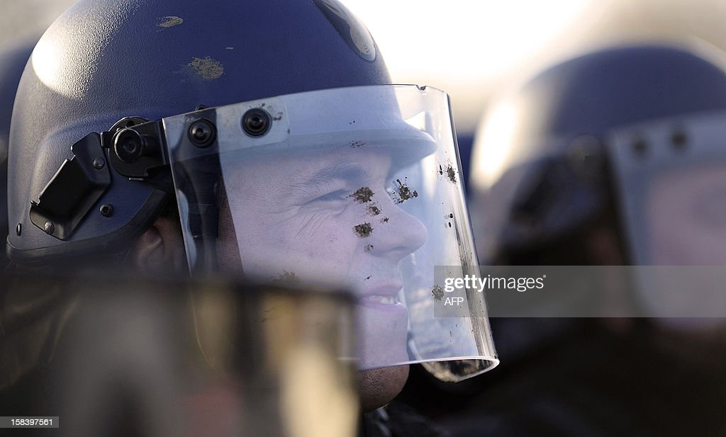 A French gendarme, wearing a helmet covered with mud, faces opponents to the project of an international airport in Notre-Dame-des-Landes face French gendarmes on December 15, 2012, in Notre-Dame-des-Landes, western France. French court ordered on December 12, 2012 the expulsion of the opponents to the airport that is supposed to open in 2017.