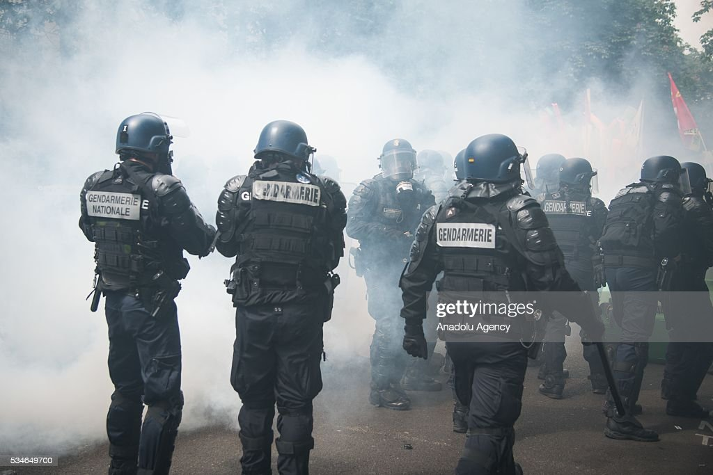 French gendarmerie interferes to the protestors with tear gas during the protest against French government's labor law reform in Paris, France on May 26, 2016.