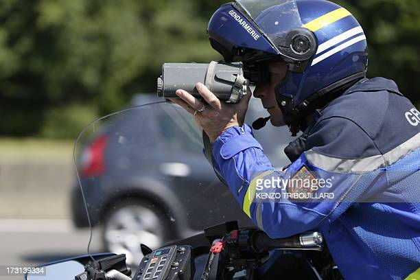 A French Gendarmerie motorcyclist uses a radar gun to check the speed of cars driving on July 6 2013 during a traffic control and survey on the A6A31...