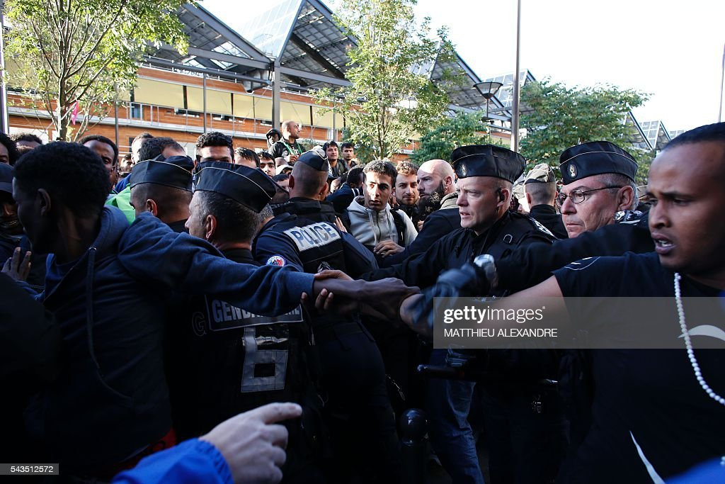 French Gendarmerie proceeds to the evacuation of migrants at the Pajol hall on June 29, 2016 in Paris. The police started early on June 29, 2016, the evacuation of several hundreds of migrants, in a camp at the former SNCF Hall 'Pajol'. / AFP / MATTHIEU