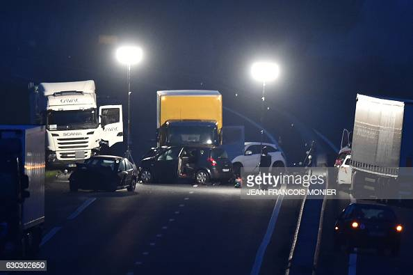 French gendarmes and emergency workers work at night at the site of a car accident involving around fifty vehicles which killed 5 people and injured...