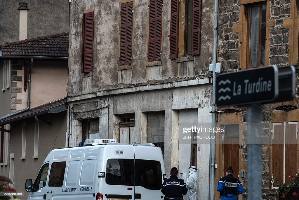 French gendarmes and forensic stand next to a gendarmerie vehicle at the entrance of the building where a mother of three was found dead on May 29, 2016 in Pontcharra-sur-Turdine, near Lyon, central eastern France. The woman's ex-husband, who took the children to his sister's house then surrendered to police, is in custody. Earlier in the day the 'Plan Alerte Enlevement', for an abduction alert procedure, was triggered following the disparition of the three children. / AFP / JEFF