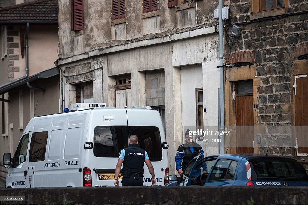 French gendarmes and forensic stand next to gendarmerie vehicles at the entrance of the building where a mother of three was found dead on May 29, 2016 in Pontcharra-sur-Turdine, near Lyon, central eastern France. The woman's ex-husband, who took the children to his sister's house then surrendered to police, is in custody. Earlier in the day the 'Plan Alerte Enlevement', for an abduction alert procedure, was triggered following the disparition of the three children. / AFP / JEFF