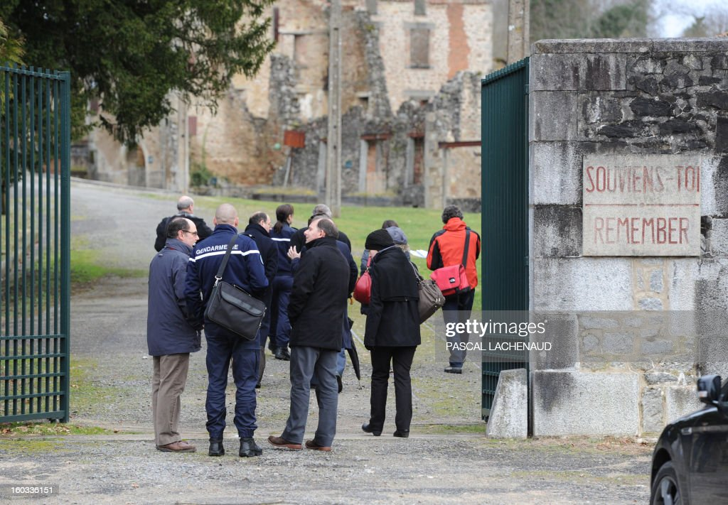 French gendarmes and Germany's investigators enter the ruins site of the village of Oradour-sur-Glane, southern France, on January 29, 2013. An investigation for crimes of war is led by German and French authorities 68 years after the 1944 massacre. On June 10, 1944, a detachment of the SS Das Reich division were ordered to destroy the village and all of its inhabitants, killing 642 persons. AFP PHOTO PASCAL LACHENAUD