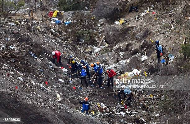 French gendarmes and investigators work on March 26 2015 in the scattered debris on the crash site of the Germanwings Airbus A320 that crashed in the...
