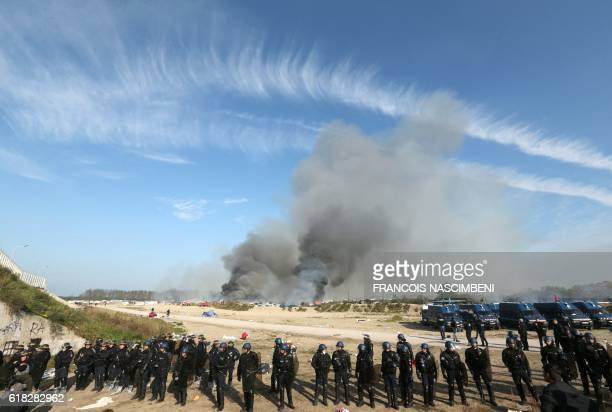 French gendarmes arrive as smoke rises from fires at the 'Jungle' migrant camp in Calais northern France on October 26 during a massive operation to...