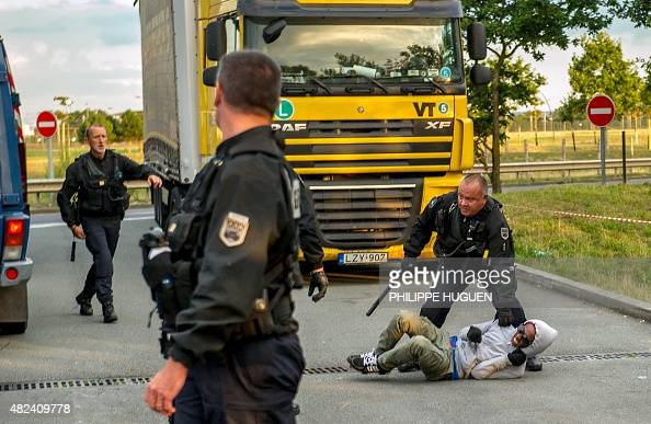 French gendarmes attempt to block a migrant after he entered the Eurotunnel site in Coquelles near Calais northern France on July 30 2015 French...