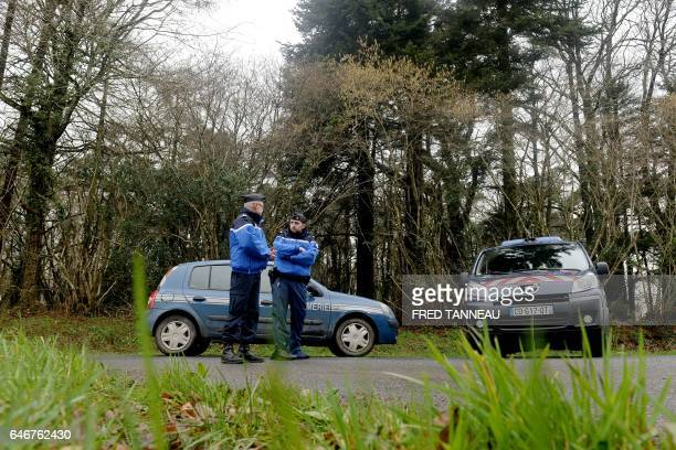 French gendarmes block the access to a road where a healthcare card in the name of Charlotte Troadec has been discovered by a runner on March 1 in...