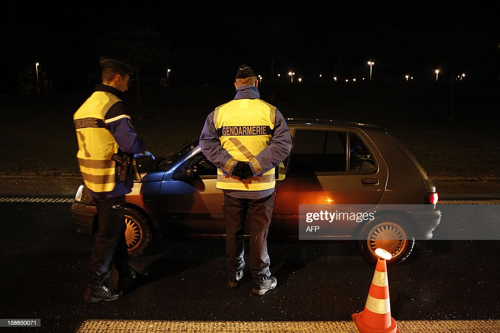 French gendarmes control a driver during the New Year's night on January 1, 2013 in Breteville-sur-Odon, near the northwestern city of Caen.
