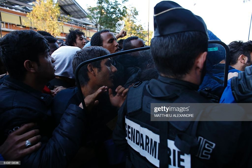 French Gendarmes evacuate a camp of migrants at the Pajol hall on June 29, 2016 in Paris. The police started early on June 29, 2016, the evacuation of several hundreds of migrants, from a camp at the former SNCF Hall 'Pajol'. / AFP / MATTHIEU