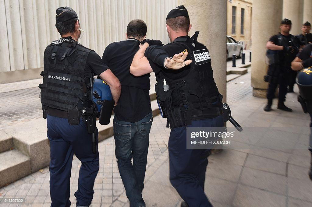 French gendarmes expell a demonstrator on June 29, 2016 in Bordeaux, southwestern France, during a French Agriculture minister and Government spokesperson public meeting. / AFP / Mehdi FEDOUACH
