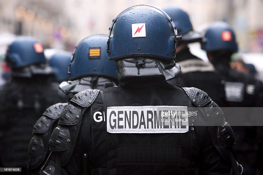 French Gendarmes from an anti riot unit (gendarmes mobiles) are in faction as workers of PSA Peugeot Citroen car maker demonstrate, on February 14, 2013 in Paris, to protest against the group's restructuring involving the loss of 11,000 jobs between 2012 and 2014 and the closure of two plants, in Brittany and in Northwest of Paris.
