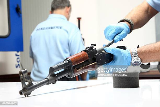 French gendarmes from UNPOL examine an AK47 assault rifle recovered on terrorists during a siege at the luxury Radisson Blu hotel that left at least...
