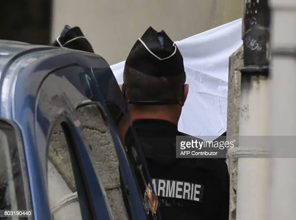 French gendarmes hold a white sheet as they prepare to escort a vehicle carrying Murielle Bolle outside the courthouse of Dijon on June 29 where she...