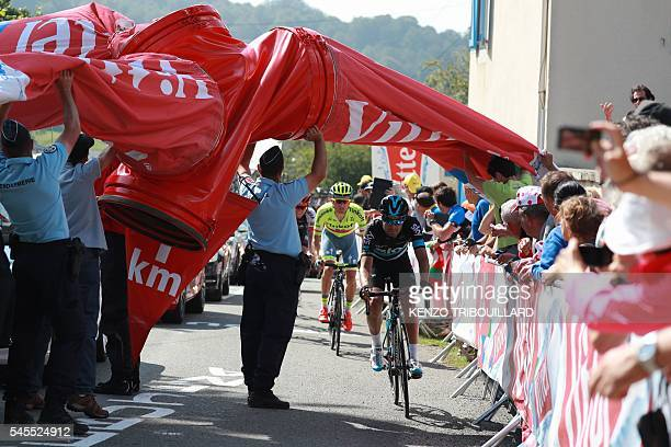 French gendarmes hold up the last kilometer deflated arch as cyclists ride during the 1625 km seventh stage of the 103rd edition of the Tour de...